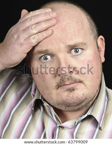 photo male under strress with hand to head on black - stock photo