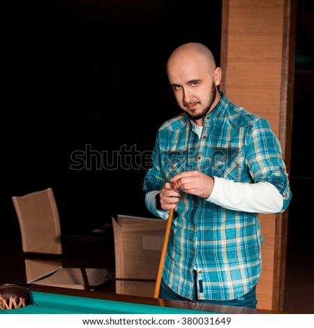 Photo man carefully rubs cue chalk. Billiard sport concept. American pool billiard. Pool billiard game. - stock photo