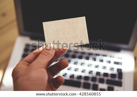 Photo Man Showing Blank Craft Business Card and Using Modern Laptop Blurred Background. Mockup Ready for Private Information. Sunlight Reflections Surface Gadget. Horizontal mockup