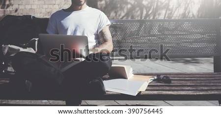 Photo man sitting city park bench and using laptop wireless internet. Studying at the University, working new project. Using book, generic design computer. Wide - stock photo