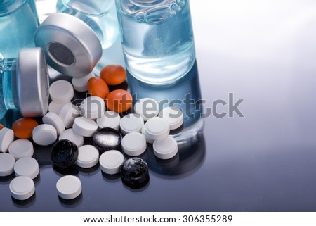Photo medical vials for storage of medicines on a black mirrored background with bright reflections. Pills. - stock photo