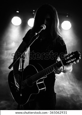 Photo of a backlit young man with long hair in silhouette playing an acoustic guitar on stage. - stock photo