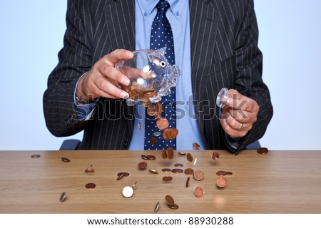 Photo of a banker sat at his desk emptying coins from his piggy bank. - stock photo
