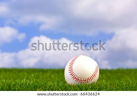 Photo of a baseball on grass with sky background. - stock photo