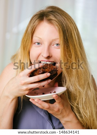 Photo of a beautiful blond woman in her early thirties with log blond hair eating a large piece of brownie or cake. - stock photo
