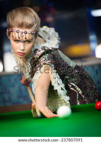 Photo of a beautiful blonde holding a pool cue and playing pool - stock photo