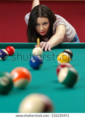 Photo of a beautiful brunette about to shoot pool. - stock photo