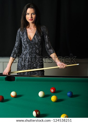 Photo of a beautiful brunette holding a pool cue and playing pool. - stock photo