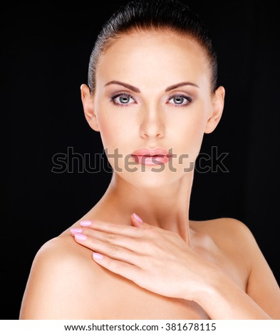 Photo of a Beautiful  face of the adult pretty woman with fresh skin - over black background - stock photo