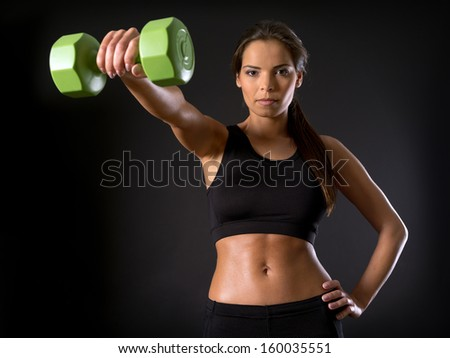 Photo of a beautiful female doing a front shoulder fly with a dumbbell over a dark background. - stock photo