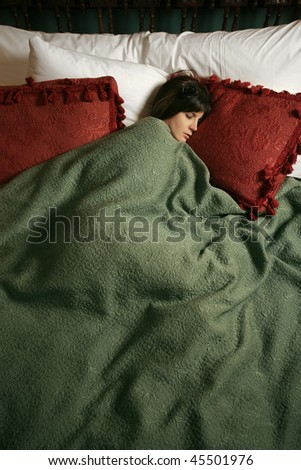 Photo of a beautiful female sleeping alone in a large bed. - stock photo