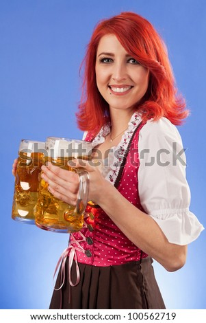 Photo of a beautiful female waitress wearing traditional dirndl and holding two mass beer steins. - stock photo