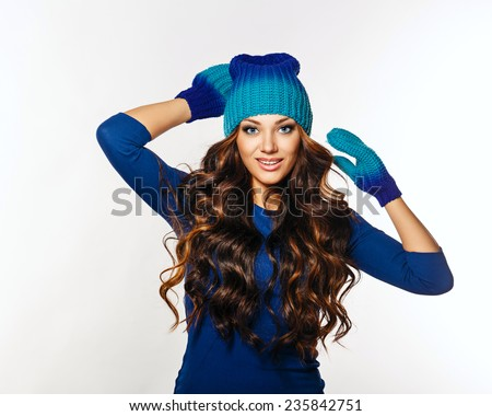 Photo of a beautiful girl with long hair dressed in a knitted hat and mittens, glamor. The girl looks contented and successful. - stock photo