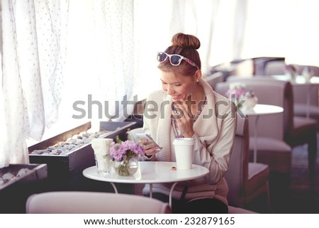 Photo of a beautiful happy young woman using wireless internet, surfing the net via smartphone and drinking coffee in a cafe in the morning. - stock photo