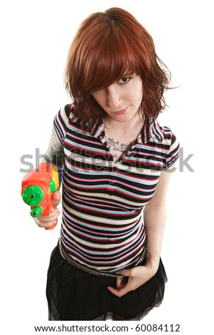 Photo of a beautiful redhead about to shoot a water gun. - stock photo