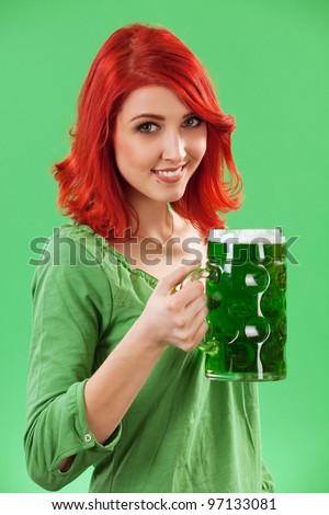 Photo of a beautiful redhead holding a huge mug of green beer for St. Patricks Day celebrations. - stock photo