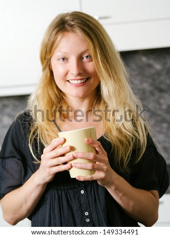Photo of a beautiful smiling blond female in her kitchen holding a large coffee.  - stock photo