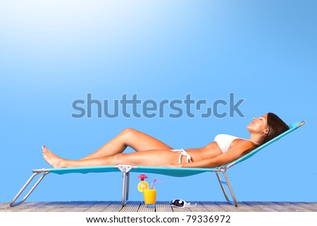 Photo of a beautiful woman in white bikini lying on a sun lounger sunbathing in the sunshine - stock photo
