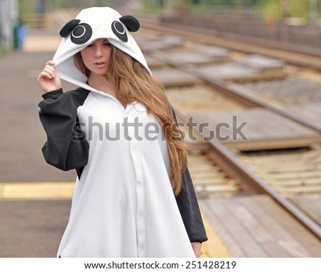 Photo of a beautiful young brunette woman standing at train station or platform wearing a bright panda bear costume - stock photo