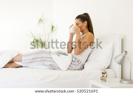 Photo of a beautiful young woman drinking coffee at home in her bed wearing pajamas while checking her laptop