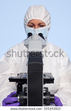 Photo of a biochemist looking at a laboratory microscope. - stock photo