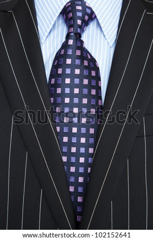 Photo of a black pinstripe suit with blue striped shirt and purple and blue patterned tie - stock photo