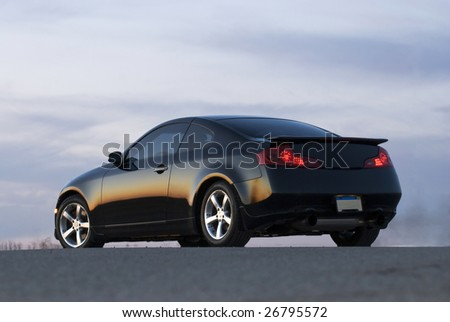 Photo of a black sports car with its tail lights on - stock photo
