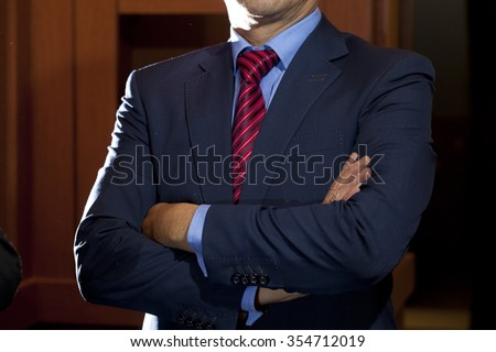 Photo of a black suit with blue shirt and red and blue patterned tie - stock photo