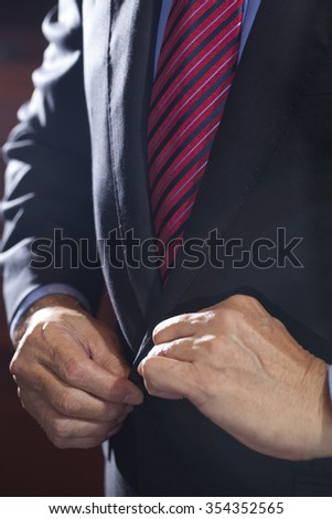Photo of a black suit with white shirt and red and blue patterned tie - stock photo