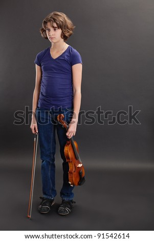 Photo of a bored young girl standing with her violin. - stock photo