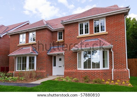 Photo of a brand new unoccupied detached red brick built five bedroom house on a modern housing development. - stock photo