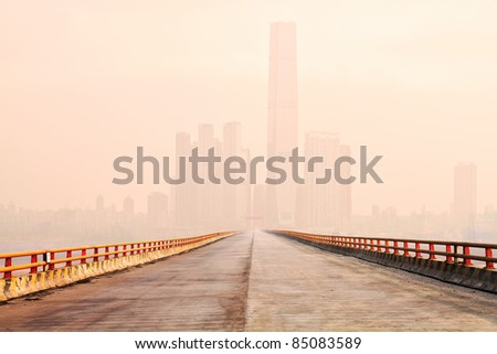 Photo of a bridge leading to the downtown of an international modern city in the fog morning - stock photo