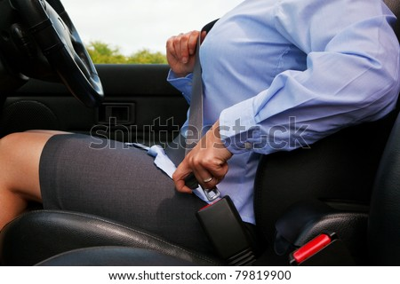 Photo of a business woman sitting in a car putting on her seat belt - stock photo
