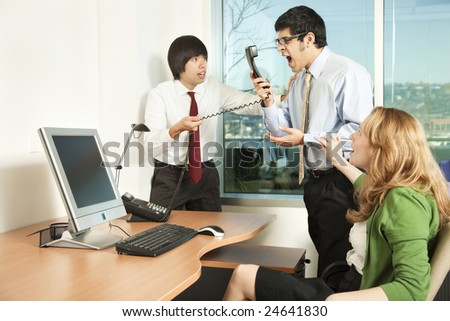 Photo of a businessman losing his temper on a phone call in front of his colleagues. - stock photo