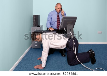 Photo of a businessman using a work experience employee for his desk - stock photo