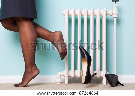 Photo of a businesswomans legs with stockings on kicking her high heel shoes off as she returns home after a hard day at work. Motion blur on one of the shoes. - stock photo