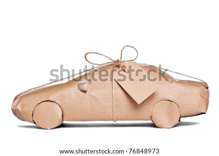 Photo of a car wrapped in brown recycled paper with label, cut out on a white background. - stock photo