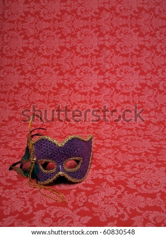 photo of a carnival mask on red decorative fabric that includes copy and cropping space - stock photo