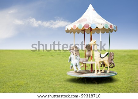 photo of a carousel for kids on grass field - stock photo