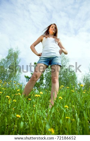 Photo of a casual teen standing confidently  in dandelion meadow