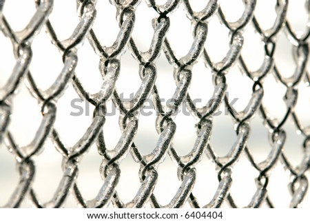 Photo of a chain link fence after an ice storm. - stock photo