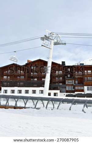 Photo of a chair lift on a mountainous ski resort as used by skiers and snowboarders in winter. - stock photo