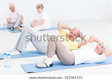 Photo of a cheerful elderly couple performing crunches on exercise mats, while another couple is resting in the blurry background - stock photo