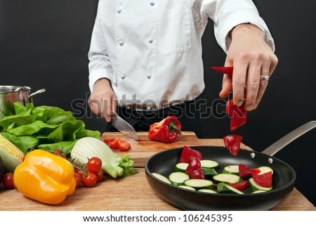 Photo of a chef adding chopped vegetables to a pan. - stock photo