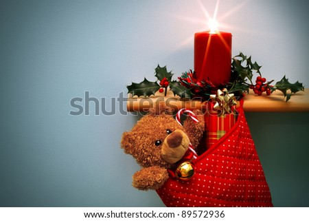 Photo of a Christmas stocking filled with presents and a candle surrounded by holly, the star from the flame was done in camera. The teddy is generic and is not a brand name bear. Copy space on left. - stock photo
