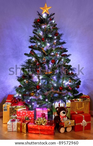 Photo of a Christmas tree with decorations and fairy lights surrounded by presents on a wooden floor. The teddy bear is generic and is not a known brand. - stock photo