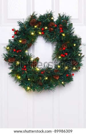 Photo of a Christmas wreath with fairy lights hanging on a white door. - stock photo