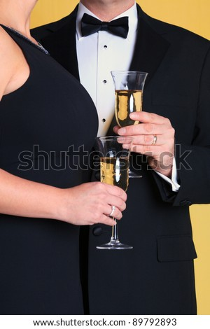 Photo of a couple in black tie evening dress holding a glass of champagne. - stock photo
