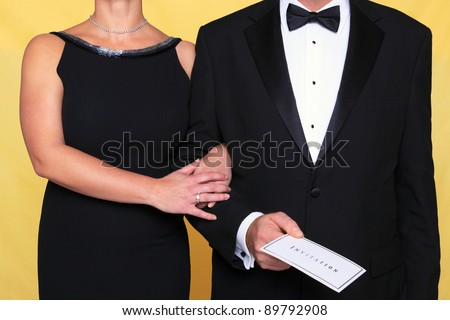 Photo of a couple in black tie evening wear, the man is holding an invitation. - stock photo