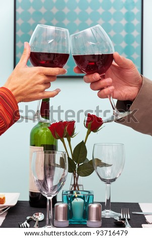 Photo of a couples hands toasting their glasses of red wine over the table in a restaurant - stock photo